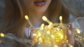 美丽的女孩对墙壁,拿着诗歌选,圣诞灯的女孩 股票录像