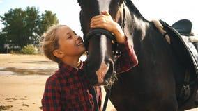 美丽的女孩对她的在海滩的马关心 在女孩的重点 股票录像