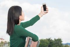 美丽的女孩年轻人 兴高采烈的俏丽的女孩selfie,当坐椅子时 免版税图库摄影
