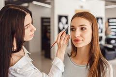 美丽的女孩得到了眼眉的更正在美容院的 免版税库存图片