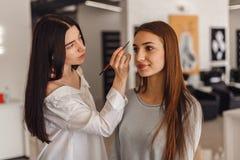 美丽的女孩得到了眼眉的更正在美容院的 图库摄影