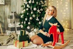 美丽的女孩微笑的年轻人 相当白肤金发的藏品她的坐在树附近的圣诞节礼物 免版税库存照片