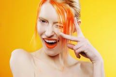 美丽的女孩情感画象有橙色头发的在橙色背景 免版税库存图片