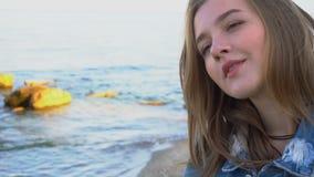 美丽的女孩慢动作画象有在照相机摆在的轻的微笑的在嘴唇,站立反对蓝色海和 影视素材