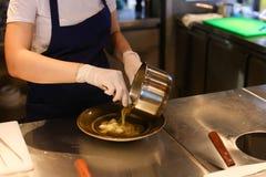 年轻美丽的女孩手厨师倾吐在c的碗现成的饭食 免版税库存图片