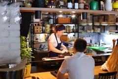 年轻美丽的女孩手厨师倾吐在c的碗现成的饭食 免版税库存照片