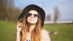 美丽的女孩投入太阳镜和姿势 大黑帽会议,时兴地穿戴的愉快和微笑的可爱的女孩 外面 影视素材