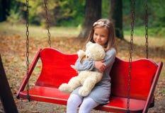 美丽的女孩拥抱一头可笑的熊 库存照片