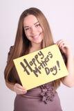 美丽的女孩拿着与词愉快的母亲节的一张桌 免版税库存图片