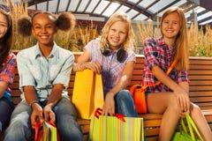 美丽的女孩拿着在长凳的购物袋 库存照片