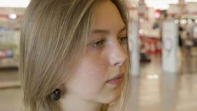 美丽的女孩拿着购物袋,使用一个巧妙的电话并且微笑着,当做购物在购物中心时 影视素材