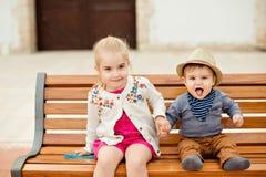 美丽的女孩握兄弟笑的男婴的手a的 库存照片