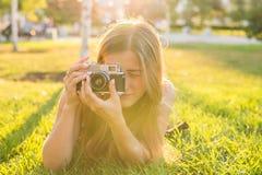 美丽的女孩摄影师在公园在春天举行一台照相机和说谎在草户外 概念  库存图片