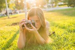 美丽的女孩摄影师在公园在春天举行一台照相机和说谎在草户外 概念  免版税库存图片