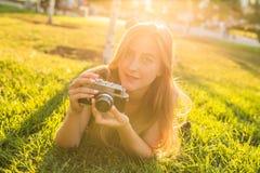 美丽的女孩摄影师在公园在春天举行一台照相机和说谎在草户外 概念  图库摄影