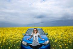 美丽的女孩支持在一个黄色领域的汽车 库存照片