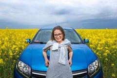 美丽的女孩支持在一个黄色领域的汽车 免版税图库摄影