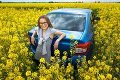 美丽的女孩支持在一个黄色领域的汽车 免版税库存照片