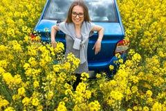 美丽的女孩支持在一个黄色领域的汽车 库存图片