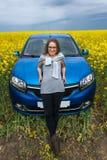 美丽的女孩支持在一个黄色领域的汽车 免版税库存图片