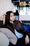 美丽的女孩放松的坐在咖啡馆的VIP长沙发 免版税图库摄影