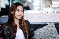 美丽的女孩放松的坐在咖啡馆 免版税库存图片