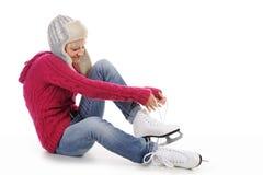 美丽的女孩放置冰鞋 库存照片