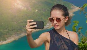 美丽的女孩旅客采取一selfie有海视图在高度 库存照片