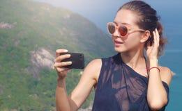 美丽的女孩旅客采取一selfie有海视图在高度 免版税库存图片