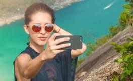 美丽的女孩旅客采取一selfie有海视图在高度 库存图片