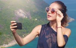 美丽的女孩旅客采取一selfie有海视图在高度 免版税库存照片
