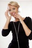 美丽的女孩是听到音乐 免版税库存照片