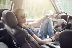 美丽的女孩是在汽车的轮子的后司机 免版税库存照片