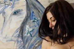 美丽的女孩是有一只被绘的独角兽的一位艺术家 免版税库存照片