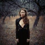 美丽的女孩有摆在森林的卷发的黑葡萄酒礼服的 在森林里丢失的减速火箭的礼服的妇女让参议员担心 库存照片