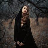 美丽的女孩有摆在森林的卷发的黑葡萄酒礼服的 在森林里丢失的减速火箭的礼服的妇女让参议员担心 免版税库存图片
