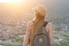 美丽的女孩有背包的和从看老城市的高度的一个帽子的 回到视图 免版税库存图片
