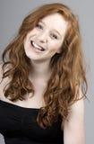美丽的女孩朝向红色微笑 免版税图库摄影