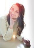 美丽的女孩松弛近的窗口 黑暗的长的卷发 免版税库存图片