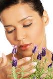 美丽的女孩气味淡紫色花 免版税库存图片