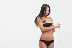 年轻美丽的女孩测量您的轮盘赌的身体局部 免版税库存图片