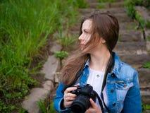 美丽的女孩游人坐葡萄酒石头步和与一台专业照相机的采取照片在刮风的天气 库存照片