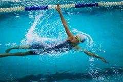 年轻美丽的女孩游泳仰泳 图库摄影