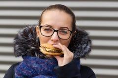 美丽的女孩热切地吃在街道上的一个汉堡包 库存照片