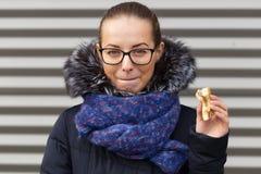 美丽的女孩热切地吃在街道上的一个汉堡包 免版税库存图片