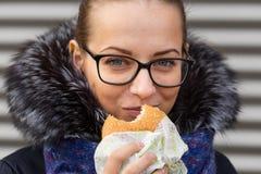 美丽的女孩热切地吃在街道上的一个汉堡包 库存图片