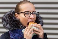 美丽的女孩热切地吃在街道上的一个汉堡包 免版税图库摄影
