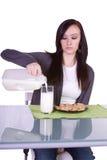 美丽的女孩玻璃她的倾吐的牛奶 免版税库存照片