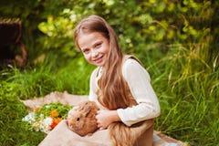 美丽的女孩用一只兔子在森林 库存图片