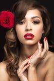 美丽的女孩用卡门西班牙方式有红色嘴唇和一朵玫瑰的在她的头发 免版税库存图片